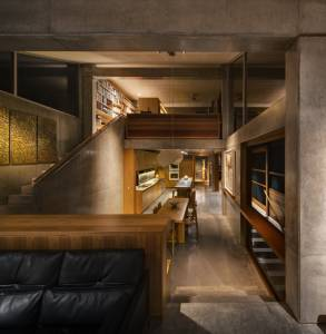 Black-leather-sofa-wooden-desk-square-wooden-dining-table-wooden-dining-chair-concrete-floor-concrete-stairway-glass-window