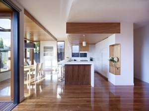 Parquet-wooden-floor-laminated-white-wall-white-ceiling-white-pendant-lamp-white-kitchen-cabinet-wooden-furniture-615x461